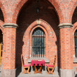 Table and chairs in a medieval arch — Stock fotografie