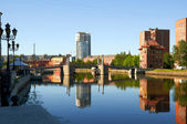Pedestrian bridge and buildings on the banks of the river Pregel — Stock Photo