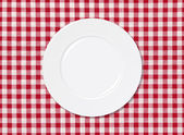 White plate on red and white striped seamless tablecloth — Stock Photo