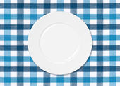 White plate on blue and white tablecloth — Foto Stock