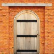 Wood door on orange brick wall — Stock Photo