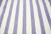 Blue and white vertical striped tablecloth — Stock Photo