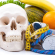 Fitness equipment and human scull — Stock Photo