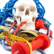 Fitness equipment and human scull — Stock Photo #13194535