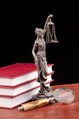 Law books, magnifying glass and lady of justice — Stockfoto