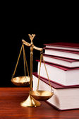 Scale of justice on wooden table and black background — Stock Photo