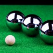Steel balls on green surface — Stock Photo