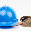 Blue hardhat, sand pile and mason trowel — Stock Photo
