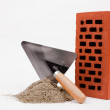 Foto Stock: Mason trowel, brick and sand pile isolated on white