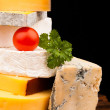 Various types of cheese and tomato on wooden table isolated on black — Stock Photo