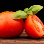 Tomato and basil on black background — Stock Photo