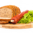 Bread and smoked sausages on wooden plate — Stock Photo