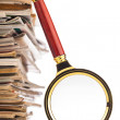 Pile of newspapers and magnifying glass — Stock Photo #38309685