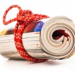 Stock Photo: Role of newspapers with red rope