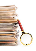 Pile of newspapers and magnifying glass — Stock Photo
