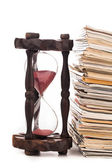Pile of newspapers and hourglass — Stock Photo