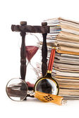 Pile of newspapers magnifying glass and hourglass — Stock Photo