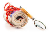 Role of newspapers with red rope and magnyfying glass — Stock Photo