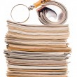 Stock Photo: Pile of newspapers and magnifying glass