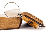Magnifying glass and old book — Stock Photo