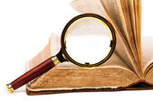Old book and magnifying glass isolated on white — 图库照片