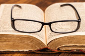 Reading glasses and old book — Stock Photo