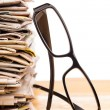 Stock Photo: Pile of newspapers and reading glasses