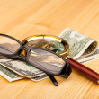 Stock Photo: Money and reading glasses