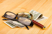Money and reading glasses — Stock Photo