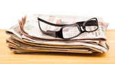 Pile of newspapers and reading glasses — Stock Photo