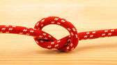 Rope knot on wooden table — Stock Photo