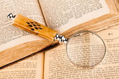 Magnifying glass and old books — Stock Photo