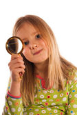 Pretty little girl looking through magnifying glass — Stock Photo