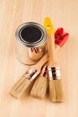 Can of paint with paintbrushes on wooden table  — Stock Photo