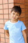 Sad boy against a brick wall — Stock Photo