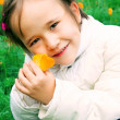 Innocent little girl with a flower in hand — Stock Photo