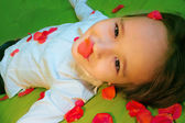Girl lying in rose petals — Stock Photo