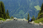 Old man sitting and looking at the mountain — Stock Photo