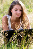 Young and happy girl with laptop in the park — Stock Photo