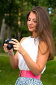 Beautiful smiling girl with camera on nature — Stock Photo
