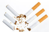 Three broken cigarette on a white background — Stock Photo