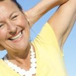 Cheerful senior woman sky background — Stock Photo