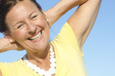 Cheerful senior woman sky background — Stock Photo