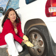 Woman changing car tyre — Stok fotoğraf