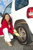 Woman changing car tyre — Stockfoto