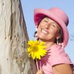 Beautiful mature lady with sunflower — Stock Photo