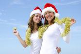 Dos mujeres celebrando navidad soleada — Foto de Stock