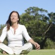 Relaxed meditating mature womoutdoor — Stock Photo #17409701
