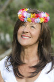 Senior woman flower in hair outdoor — Stock Photo