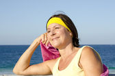 Relaxed sporty mature woman beach — Stock Photo